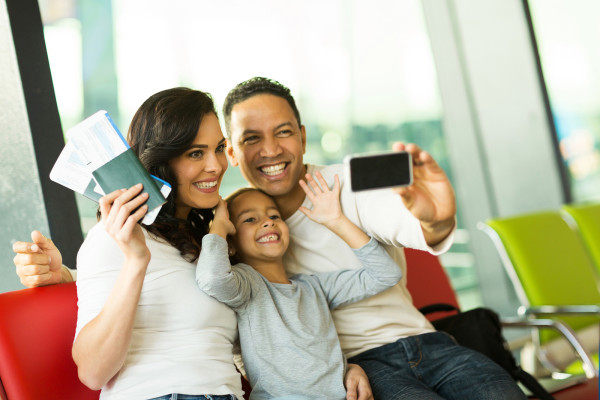 happy family at airport taking self portrait with smart phone at